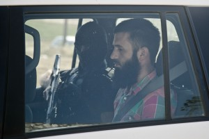 Kosovo police officers escort Milazim Haxhiaj, a suspect in a terror attack, to a court in Kosovo's capital Pristina, Sunday, July 12, 2015. Kosovo authorities say they have cut off the water supply to tens of thousands of people in the capital after police arrested five suspects linked to the Islamic State group who allegedly were planning to poison a reservoir. (AP Photo/Visar Kryeziu)