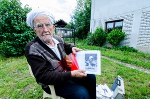Zeqir Dreshaj holds a book with a photo of Jakup Ferri, an Albanian nationalist and rebel leader from the 1880s who died in a battle against Montenegrin forces. Photo: Valerie Plesch