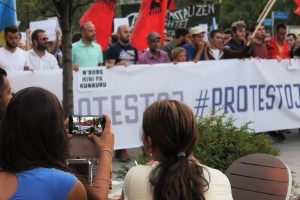 photo from the third protest, a woman drinking coffe taking picture of the protesters