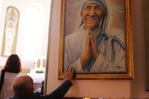 A believer touches the portrait of Mother Teresa at the Church of the Madonna of Letnica. | Photo: Rron Gjinovci