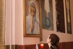 A believer looking at the portrait of Mother Teresa at the Church of the Madonna of Letnica. | Photo: Rron Gjinovci