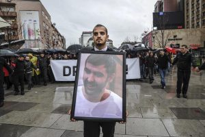 Vetevendosje activist holds a picture of Astrit Dehari. | Photo: Atdhe Mulla