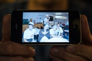 December 30, 2014 - Ferizaj, Kosovo – Dardan Marevci holds a photo taken in Afghanistan when he worked as a dishwasher (left) at Kandahar Airfield for DynCorp International. | Photo: Valerie Plesch