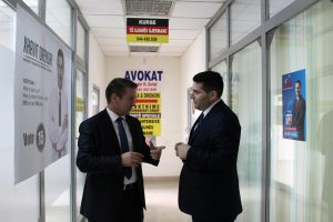 Bedri Nika, LDK candidate and Xhavit Drenori, running as an independent chit chat in front of their offices.   Photo: Rron Gjinovci
