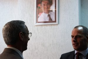 Ramiz Lladrovci and a coworker, talking in front of Kadri Veseli's picture.   Photo: Rron Gjinovci.