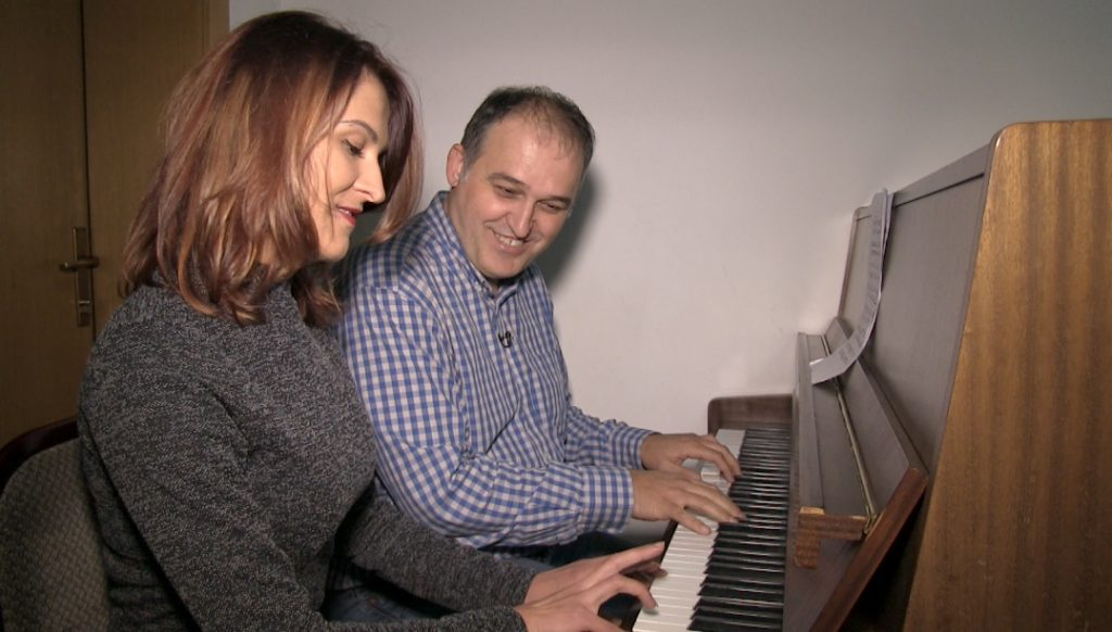 Valton Beqiri gives the article's author Sanja Sovrlic a piano lesson