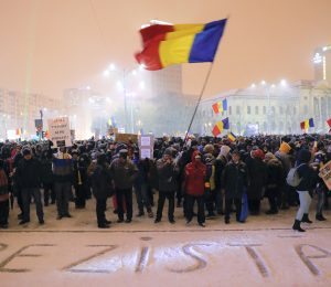 """A man waves the Romanian flag while standing with others next to the word """"We resist"""" written in the snow during a protest outside the government headquarters, in Bucharest, Romania, Wednesday, Feb. 8, 2017. 